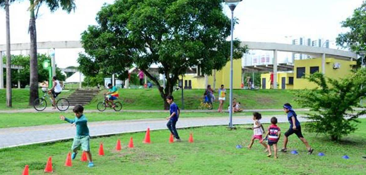 Área verde com crianças brincando e correndo no gramado