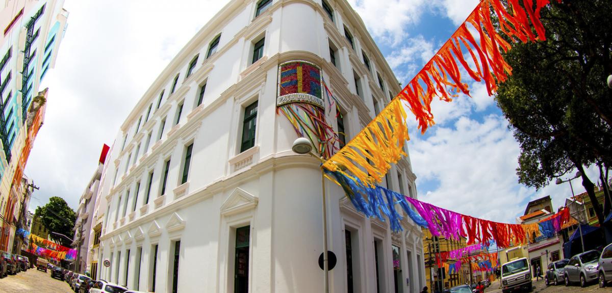 Fachada do centro cultural Paço do Frevo, em Recife. O prédio é branco com cordas coloridas penduradas em vermelho, amarelo, azul e violeta, que lembram o carnaval.